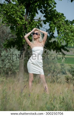 Beautiful sexy blonde girl posing on a sunny summer day at the tree