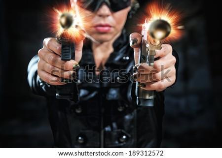 Beautiful sexy blonde girl with gun shooting - stock photo