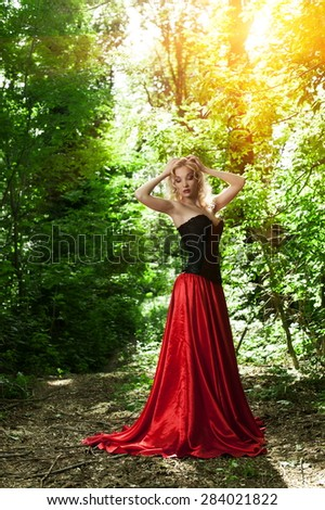 Beautiful sexy blonde in a black corset and red skirt with a long train posing in forest - stock photo