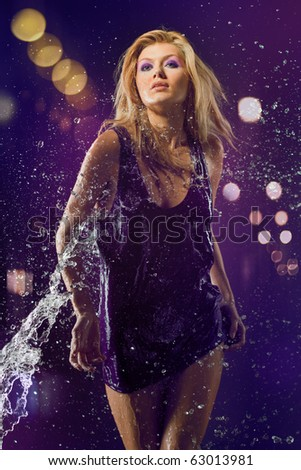 beautiful sexy blonde in a wet violet purple shirt on the naked body under a water spray