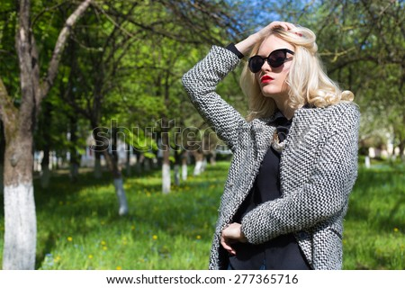 beautiful sexy blonde woman in sunglasses and a coat to go to the apple orchard on a sunny spring day - stock photo