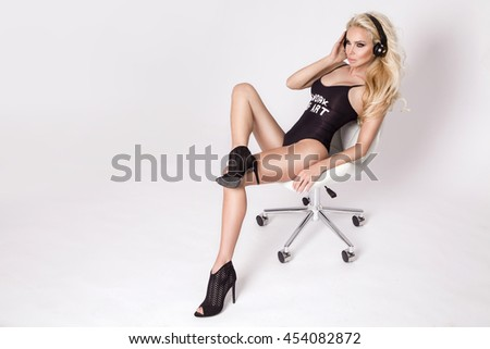 beautiful sexy blonde woman sitting in a chair wearing underwear swimsuit has ears headphones and listen to music is sensual, she have  amazing body and long legs in black long boots - stock photo