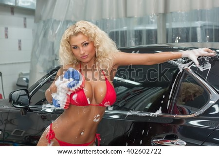Beautiful sexy blonde woman washing a car. - stock photo