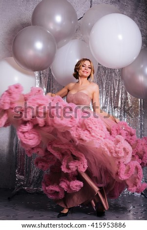 Beautiful sexy blonde young woman wearing a pink long dress. Fashionable women with attractive body creates defiantly closed. Sensual girl with big tits. - stock photo