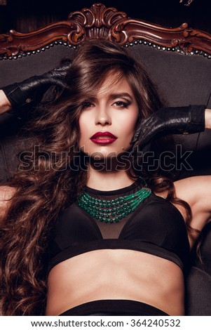 Beautiful sexy brown  curly long hair woman posing in the camera. Studio shooting in interior. Model sitting in chair. Briight make up, red lips, black lingerie. Hot glamorous brunette woman. - stock photo