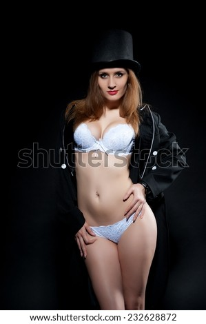 Beautiful sexy brunette girl in a black coat over his naked body and cylinder posing on a black background - stock photo