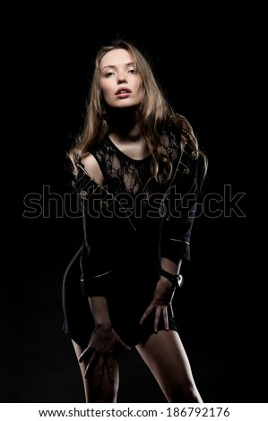 Beautiful sexy brunette girl posing on a black background in an evening dress