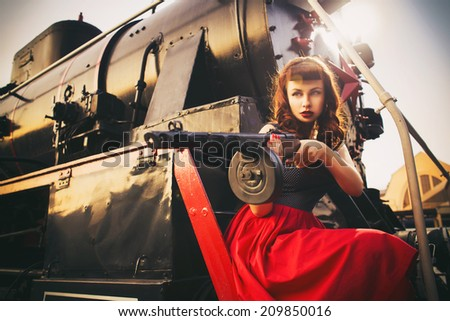 Beautiful sexy brunette retro woman with pin-up hairstyle and make-up in a shorts and shirt with a PCA gun in her hands on vintage train. Outdoors. Retro toned - stock photo