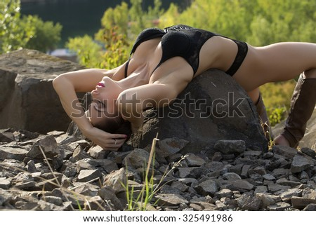 Beautiful sexy brunette with bright makeup in black body and open boots lying with closed eyes on large stone on green trees background in daytime, horizontal photo - stock photo