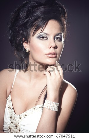 Beautiful sexy brunette woman in white dress with perfect makeup and hair - stock photo