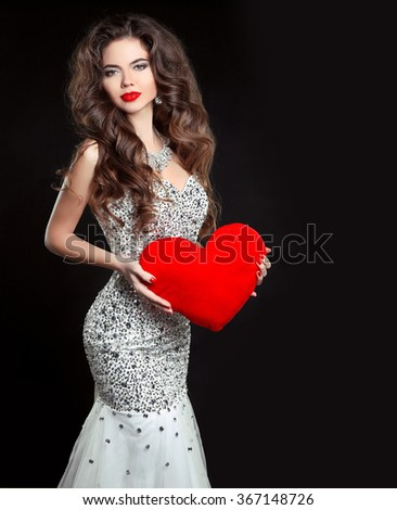 Beautiful sexy brunette Woman present red heart, Valentine's day. Elegant girl model with long wavy hair style, makeup. Lady in luxury dress isolated on black background. - stock photo
