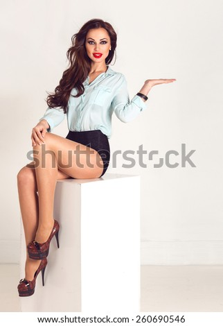 Beautiful sexy brunette woman sitting on a white cube with space board and showing empty copy space for product on the open hand palm, on a bright background.  - stock photo