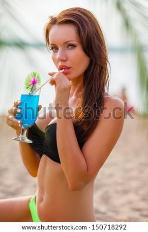 beautiful sexy brunette woman wearing bikini drinking blue cocktail - stock photo