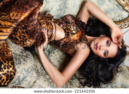 Beautiful sexy brunette woman with wavy hair in a bright multi-colored suit wild animal dress with rings bracelets accessories, or evening hairstyle and makeup lying on the bed with cushions  - stock photo