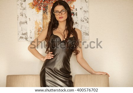 Beautiful sexy brunette young woman wearing black leather short dress. Fashionable female with attractive body posing provocatively, indoor. Sensual girl with big boobs. - stock photo