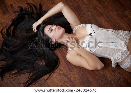 Beautiful sexy brunette young woman wearing white lingerie lying on wooden floor. Sensual gorgeous perfect body female posing provocatively, boudoir shot indoor. Attractive long hair girl in corset. - stock photo