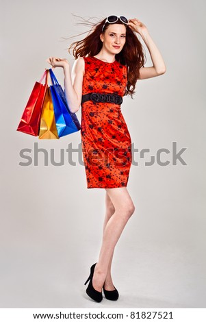 Beautiful sexy caucasian woman in stylish dress with shopping bags - stock photo
