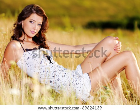 Beautiful  sexy caucasian woman sitting on the grass on summer meadow - stock photo