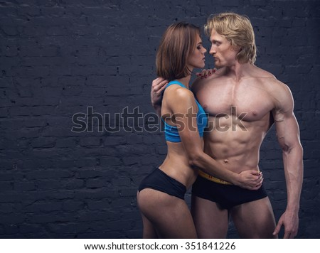 Beautiful sexy couple man and woman on a dark brick wall. Happy young couple in sexual intercourse. Young couple makes love to the wall. Athletic man. Sport couple. Young couple. Passion. Temptation. - stock photo