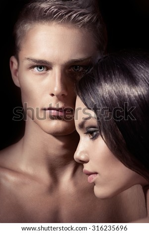 Beautiful sexy couple posing isolated on black background. Beauty fashion models couple portrait. Blonde boy with his brunette girlfriend posing in studio together. Lovers - stock photo