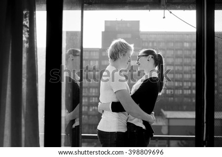 Beautiful sexy couple posing isolated on black background. Beauty fashion models couple portrait. Black-and-white portrait of a young couple in love having holidays on the city - stock photo