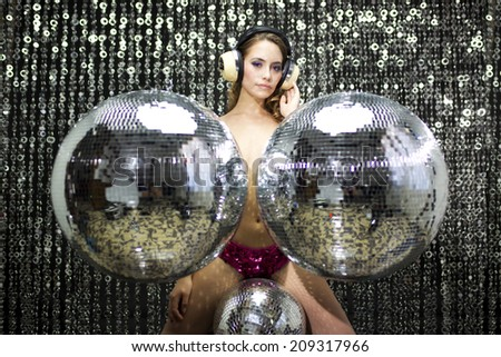 beautiful sexy disco topless woman dances and poses surrounded by discoballs. Useful for fashion, beauty, music and events  - stock photo