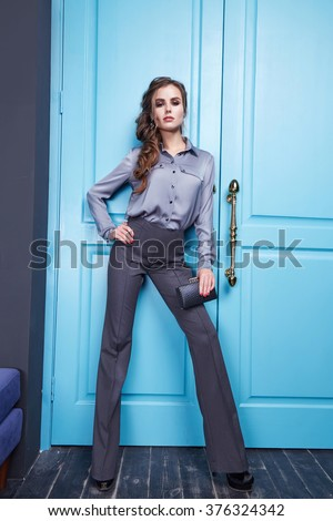 Beautiful sexy girl dressed style of fashion clothing new catalog of the collection, modern, stylish pants, fancy silk shirt accessory shoes with high heels, interior room with blue door entrance exit - stock photo