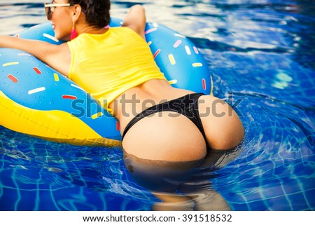 Beautiful sexy girl in a bathing suit swims in the pool on an inflatable circle in the form of a donut. Back view - stock photo