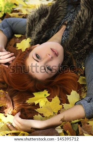 beautiful sexy girl lying on autumn leaves