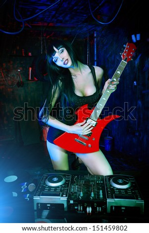 Beautiful sexy girl playing electric guitar in the old garage.  - stock photo