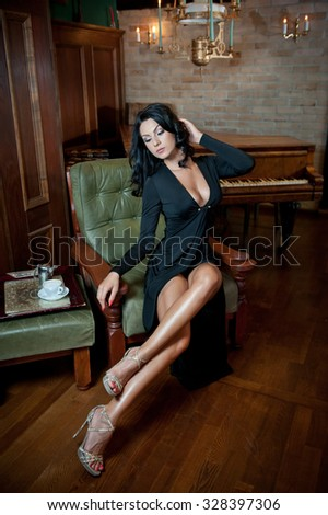Beautiful sexy girl sitting on chair and relaxing. Portrait of brunette woman with long legs posing challenging. Sensual female with black dress and high heels posing in luxurious vintage scenery - stock photo