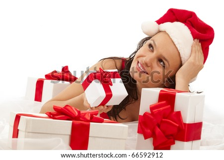 Beautiful sexy girl wearing santa hat with many gift boxes over white - stock photo