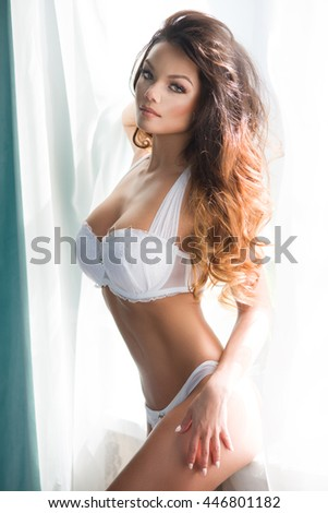 Beautiful sexy girl with perfect body standing near window