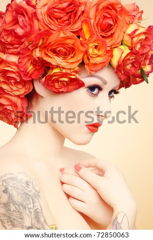 Beautiful sexy girl with tattoos and fancy wig of bright orange roses - stock photo