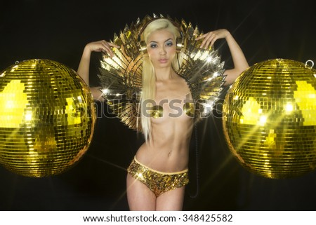 beautiful sexy gold disco woman with a speaker bra surrounded by discoballs. Perfect for stylish club, disco and fashion events  - stock photo