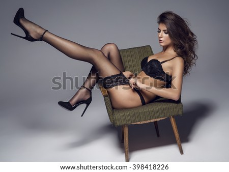 Beautiful sexy lady in elegant black lingerie and stockings. Beauty brunette woman with attractive buttocks in lace lingerie.  - stock photo