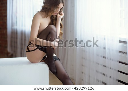 Beautiful sexy lady in elegant black panties and stockings. Fashion portrait of model indoors. Beauty blonde woman with attractive body in lace lingerie. Female ass in underwear. Close up naked girl - stock photo