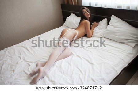 Beautiful sexy lady in elegant white panties and bra. Portrait of fashion model girl indoors. Beauty brunette woman with attractive buttocks in lace lingerie. Female ass in underwear. Naked body - stock photo