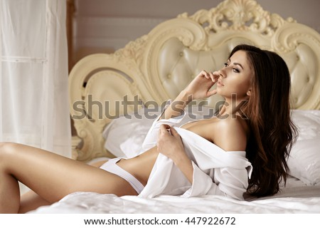 Beautiful sexy lady in elegant white panties and shirt. Portrait of fashion model girl indoors. Beauty brunette woman with attractive buttocks in lace lingerie. Female ass in underwear. Naked body - stock photo
