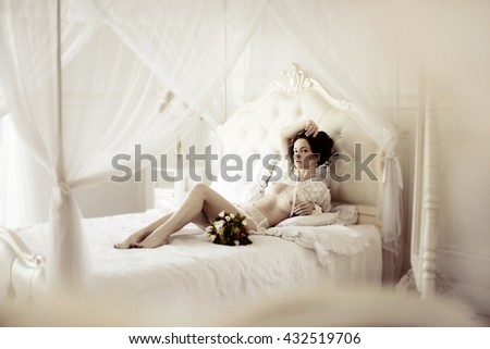 Beautiful sexy lady in elegant white panties. Fashion portrait of model with bouquet indoors. Beauty brunette woman with attractive body in lace lingerie. Female ass in underwear. Naked girl - stock photo