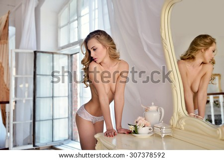 Beautiful sexy lady in elegant white panties. Portrait of fashion model girl indoors. Beauty blonde woman with attractive buttocks in lace lingerie. Female ass in underwear. Naked body - stock photo