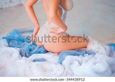 Beautiful sexy lady with perfect big breast in elegant white bodysuit. Portrait of fashion model girl indoors. Beauty woman with attractive buttocks in lace lingerie. Female ass in underwear. - stock photo