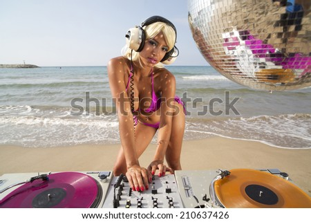 beautiful sexy latin bomb-shell djing at a beach in the early morning. useful for style fashion and music events - stock photo