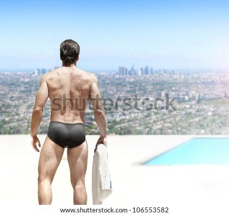 Beautiful sexy man in bikini swim suit with nice body at glamorous rooftop swimming pool - stock photo