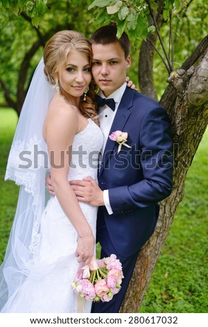 Beautiful sexy model girl in white dress. Wedding couple. Man in suit. Beauty blonde bride with brunette groom. Female and male portrait with bouquet. Woman with lace veil. Cute lady and guy outdoors