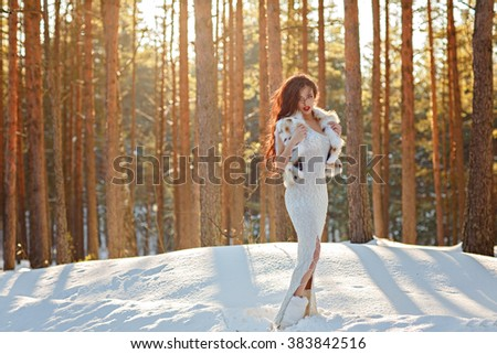 Beautiful sexy slender brunette in a white dress and a fur vest standing in a winter forest at sunset - stock photo