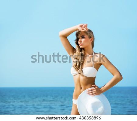 Beautiful, sexy, slim lady in alluring bikini posing with a hat on the beach.              - stock photo