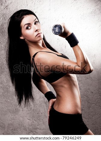 beautiful sexy sporty muscular woman with a dumbbell in the gym - stock photo
