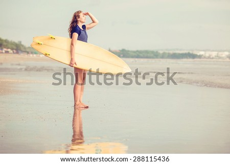 Beautiful sexy surfer girl on the beach at sunset looking for the waves from the shore with yellow surfboard ain her hands - stock photo