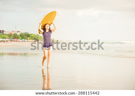 Beautiful sexy surfer girl on the beach at sunsetwalks along ocean shore with yellow surfboard in her hands in sunset light. Healthy life, sport  concept with copyspace - stock photo